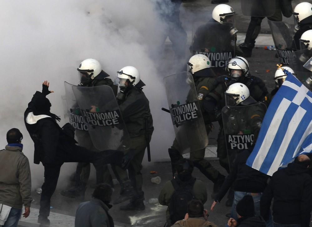 Greece: A protester kicks a police officer's shield during Sunday's anti-austerity demonstrations.