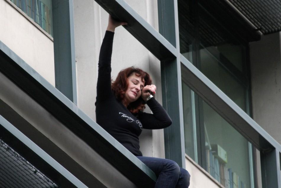An employee at a government-owned company in Athens, threatens to jump from her office window after being told she would likely be laid off. Her firm is on the list of companies to be cut as part of approved austerity measures.
