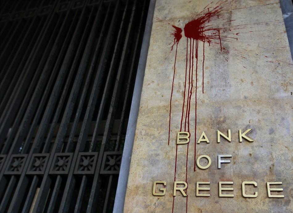 The defaced sign at Athens' Bank of Greece, a day after violent riots spread through the city.