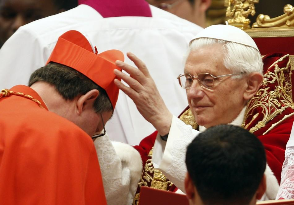 Pope Benedict XVI places a red biretta, a four-cornered hat, on the head of new Cardinal Rainer Maria Woelki of Germany