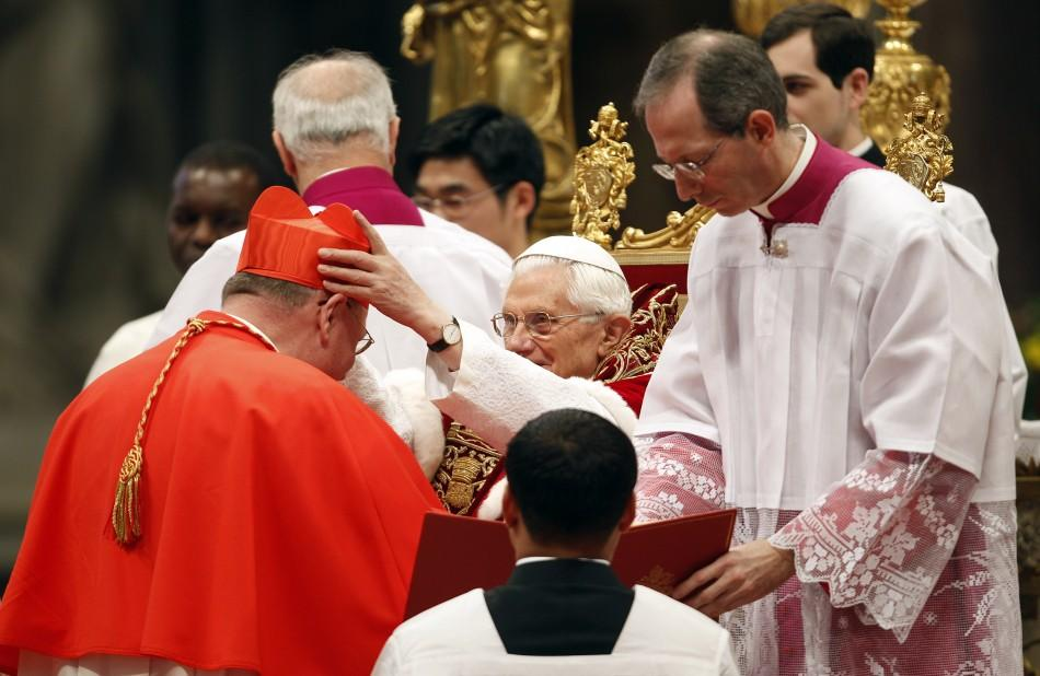 Pope Benedict XVI places a red biretta, a four-cornered hat, on the head of new Cardinal Timothy Dolan of the U.S.