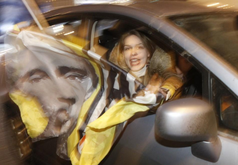 A participant holds a flag with a portrait of Russian Prime Minister Vladimir Putin during a car rally to show support for Putin's presidential candidacy in Moscow Feb. 18, 2012. Russia will go to the polls for a presidential election on March 4.