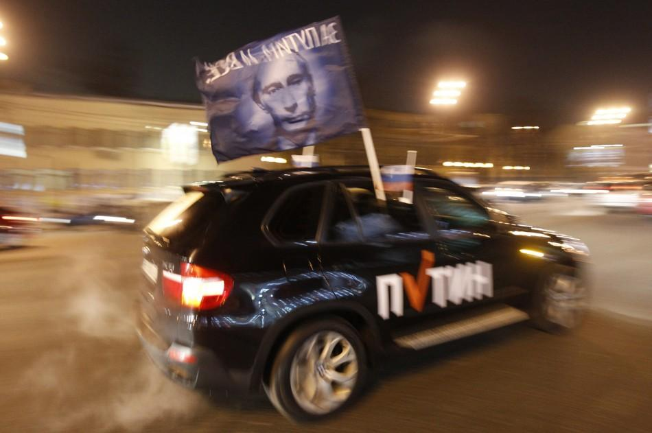 A car drives with a flag showing a portrait of Russian Prime Minister Vladimir Putin during a car rally to show support for Putin's presidential candidacy in Moscow Feb. 18, 2012. Russia will go to the polls for a presidential election on March 4