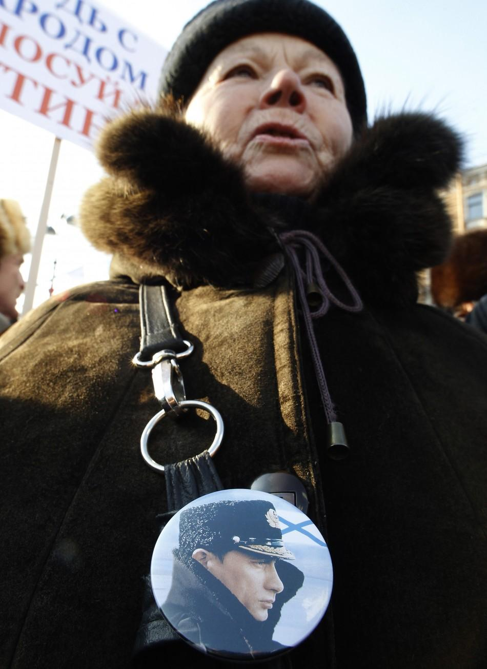 A woman wearing a badge with a portrait of Russian Prime Minister Vladimir Putin attends a rally in support of his presidential candidacy in St.Petersburg, Feb. 18, 2012.