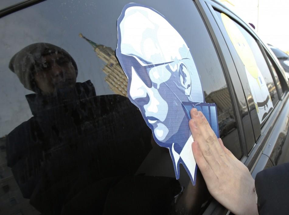 A man sticks a portrait of Russia's Prime Minister Vladimir Putin on a car before a car rally to show support for Putin's presidential candidacy in Moscow Feb. 18, 2012. Russia will go to the polls for a presidential election on March 4.