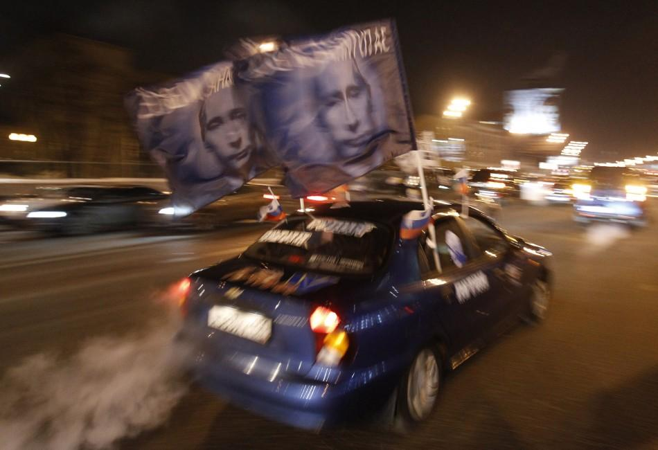A car drives with flags showing portraits of Russian Prime Minister Vladimir Putin during a car rally to show support for Putin's presidential candidacy in Moscow Feb. 18, 2012. Russia will go to the polls for a presidential election on March 4.