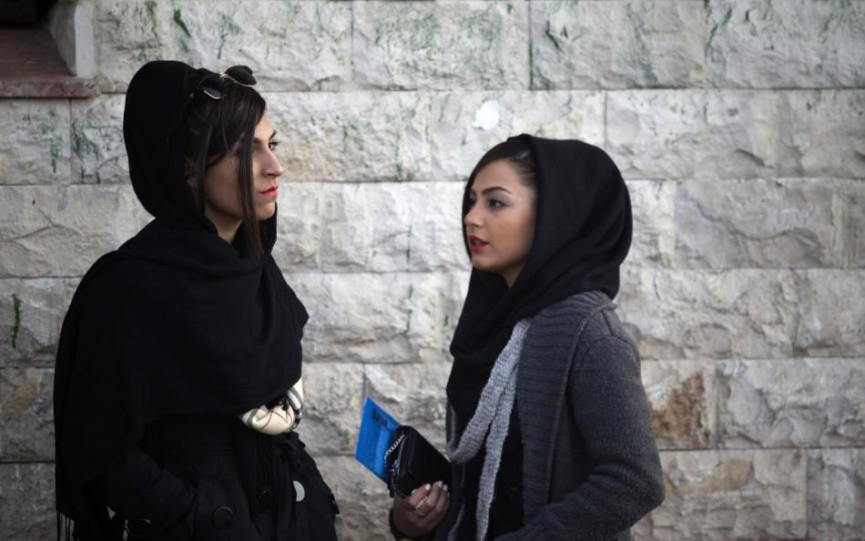 Two Iranian women talk at a corner of a square in northern Tehran