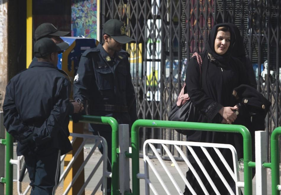 A woman walks past police officers in a square in central Tehran