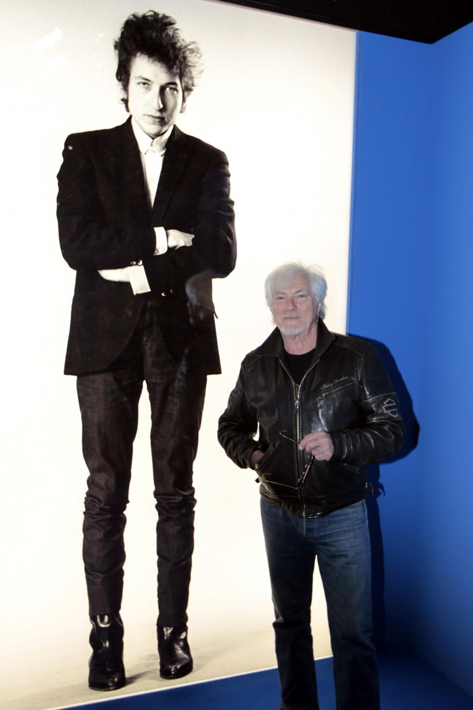 French singer Hugues Aufray poses in front of a photograph of Dylan at the museum of the Cite de la Musique in Paris
