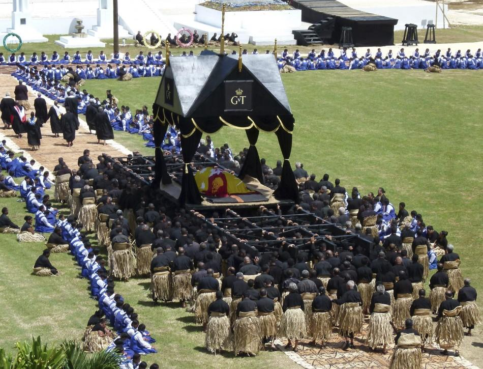 A coffin carrying Tonga's King George Tupou V is carried on a giant black and gold-topped catafalque by 150 pallbearers to the Royal Tombs in Tonga's capital Nuku'alofa March 27, 2012