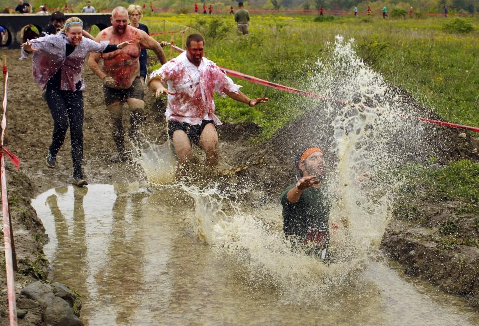 "Zombies chase a runner into a pool of water on the ""Run for Your Lives"" 5K obstacle course race in Amesbury"