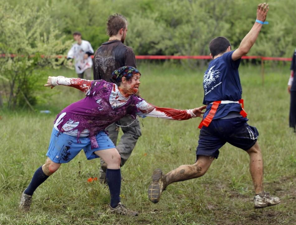 "A zombie chases a runner on the ""Run for Your Lives"" 5K obstacle course race in Amesbury"