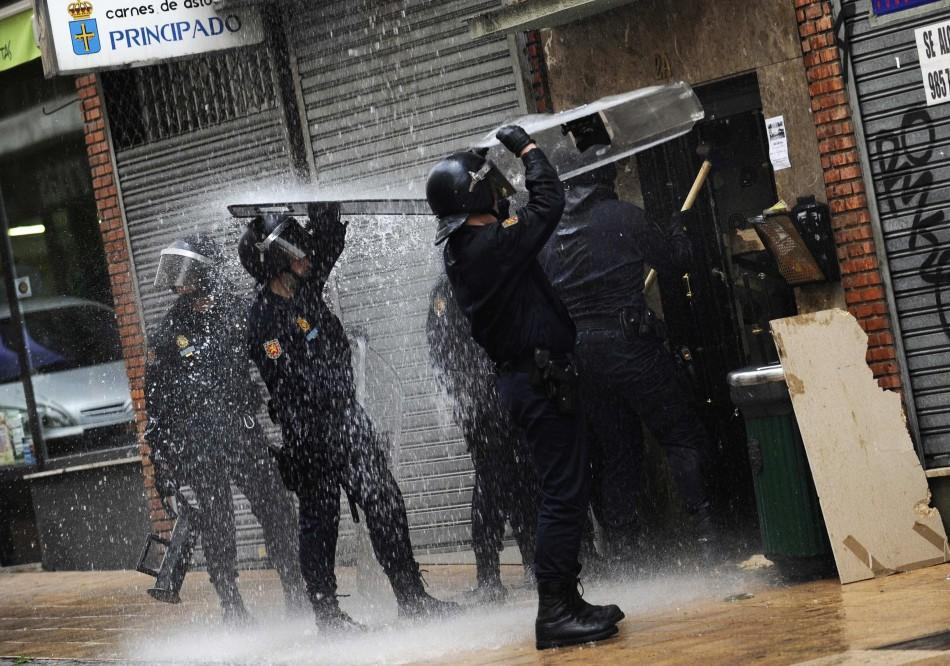 Police take cover from water dumped on them by Stop Desahucios activists during a June 27 eviciton in Oviedo, Spain.