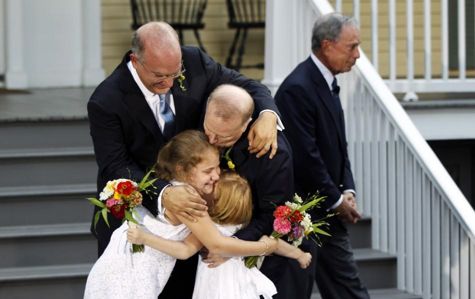 New York City Mayor Michael Bloomberg (R) walks away after presiding over the wedding of Jonathan Mintz (L), the city's consumer affairs commissioner, and John Feinblatt (C), a chief adviser to the mayor, as the newlyweds embrace their daughters Maeve (2n