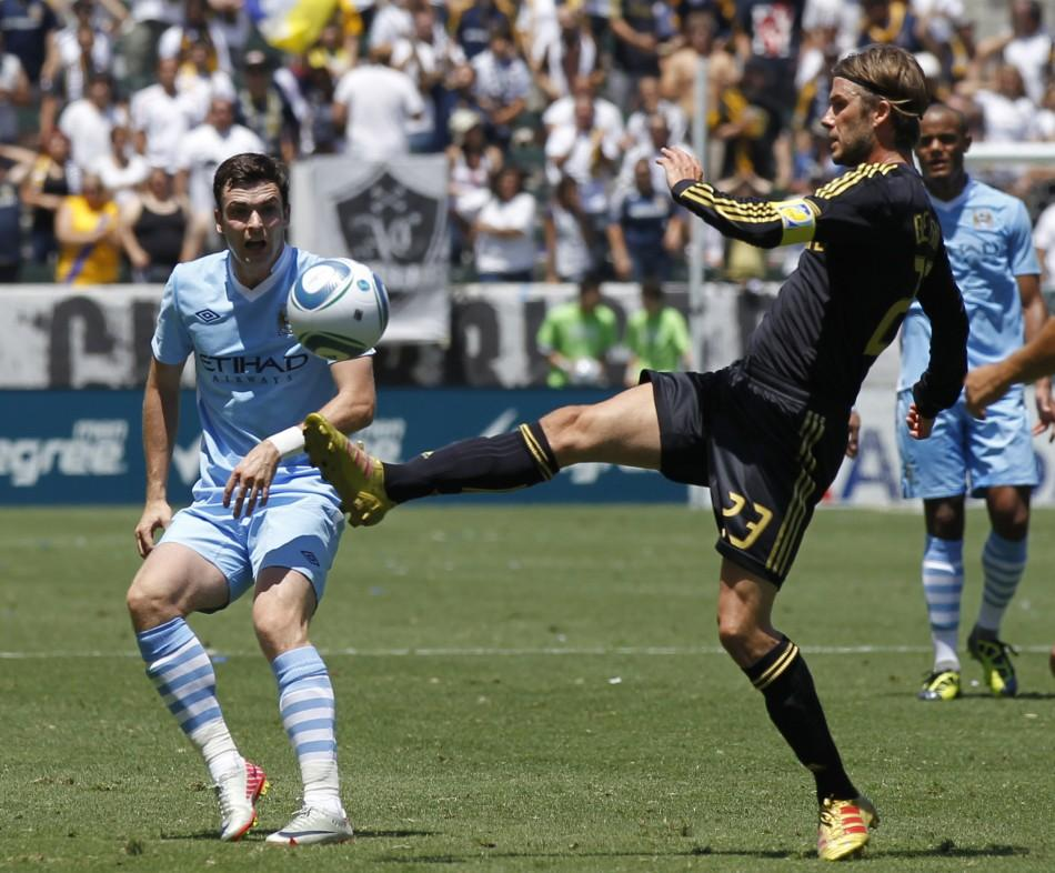 Los Angeles Galaxy's David Beckham (R) controls the ball in front of Manchester City's Adam Johnson during their World Football Challenge soccer match in Carson, California