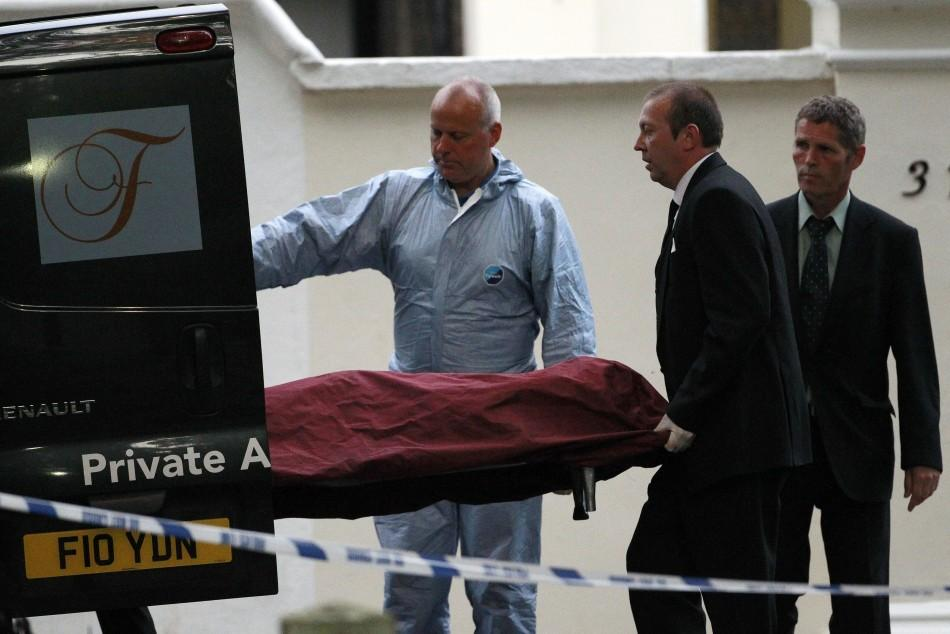 Funeral workers and apolice officer bring the body of Amy Winehouse to a van outside her house in London