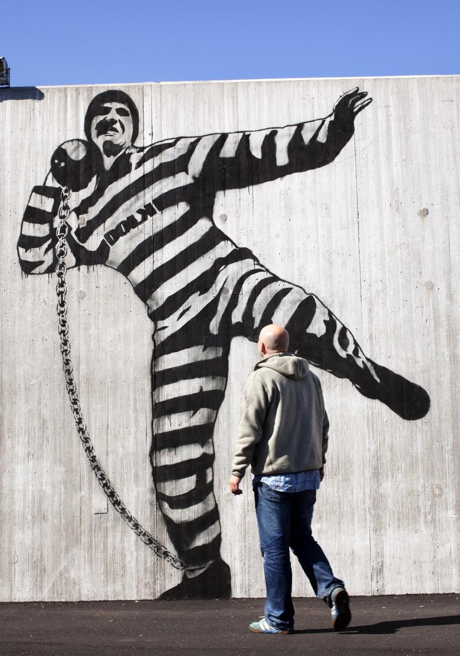 A man walks in front of graffiti inside Halden prison in the far southeast of Norway in this picture taken in 2010