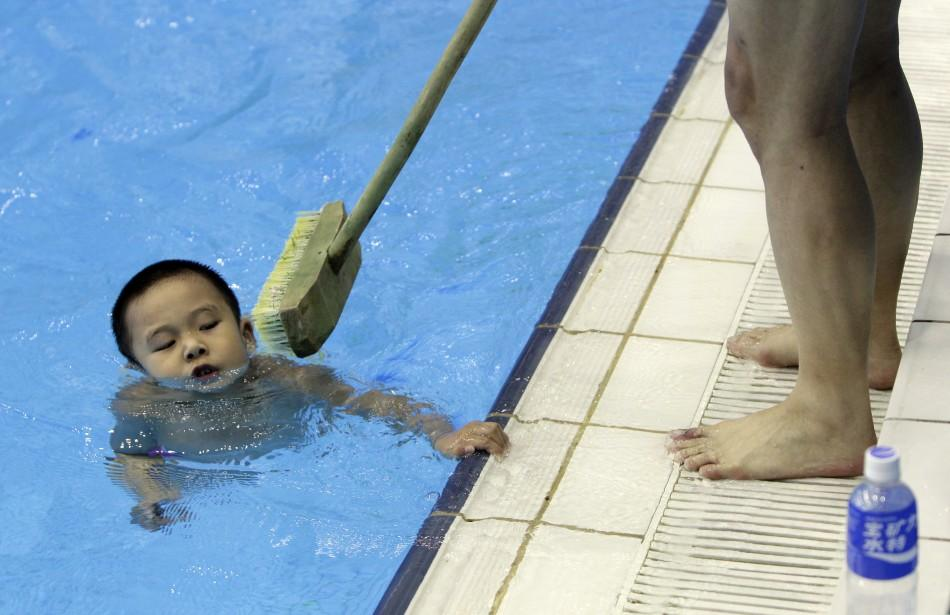 Coach holding broom tries to prevent boy from holding onto edge of pool during a diving training session at a training centre in Beijing