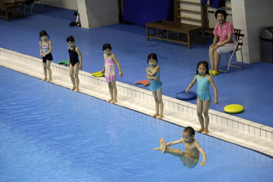 Children practise jumping into a pool during a diving training session at a training centre in Beijing