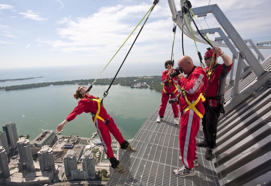 """Photographer Mark Blinch works on the catwalk during the media preview for the """"Edgewalk"""" on top of the CN Tower in Toronto"""