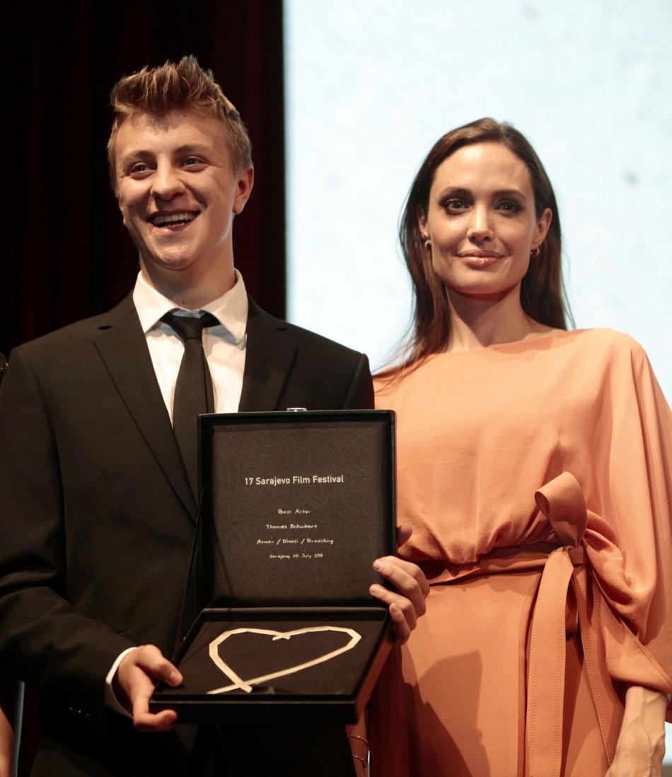 Angelina Jolie poses with Austrian actor Thomas Schubert with his award for best actor on the final night of the 17th Sarajevo Film Festival