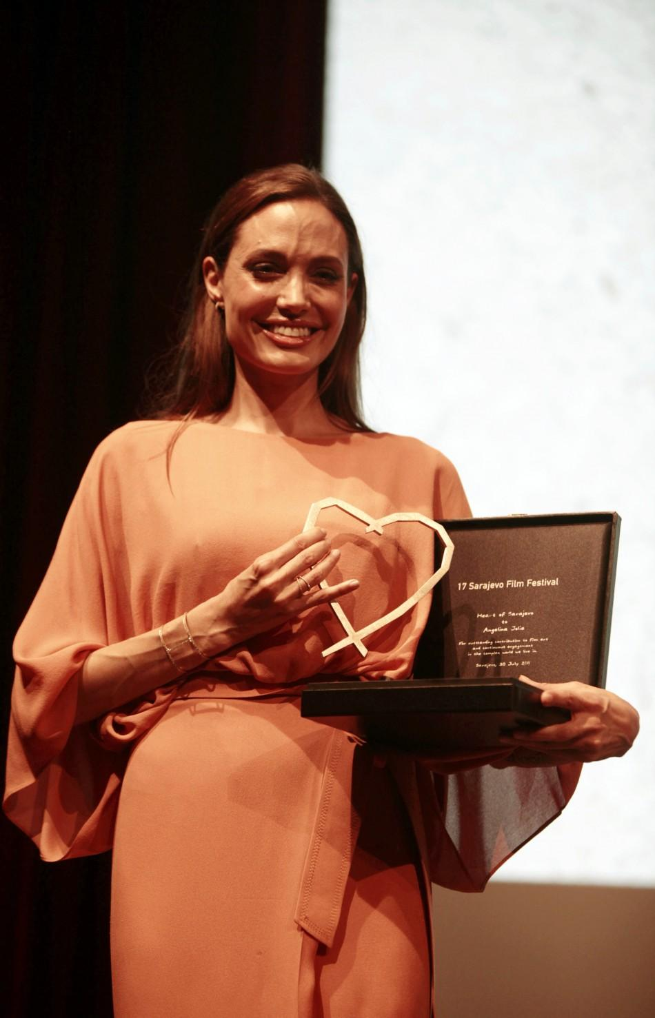 Angelina Jolie poses with the Heart of Sarajevo honorary award on the final night of the 17th Sarajevo Film Festival