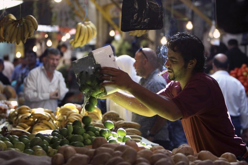 A vendor arranges limes on display as Jordanians shop in preparation for the Muslim holy month of Ramadan, at the downtown market area in Amman