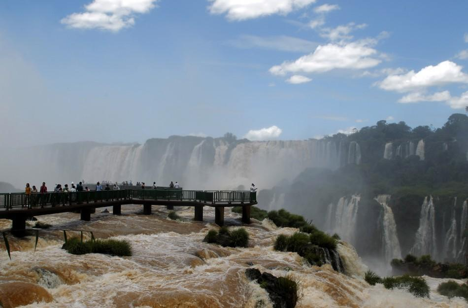 Tourists watch the Iguazu Falls from a viewing point on the border of Argentina's province of Misiones and Brazil's State of Parana