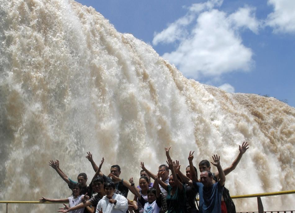 Tourists pose in front of the Iguazu Falls on the border of Argentina's province of Misiones and Brazil's State of Parana.