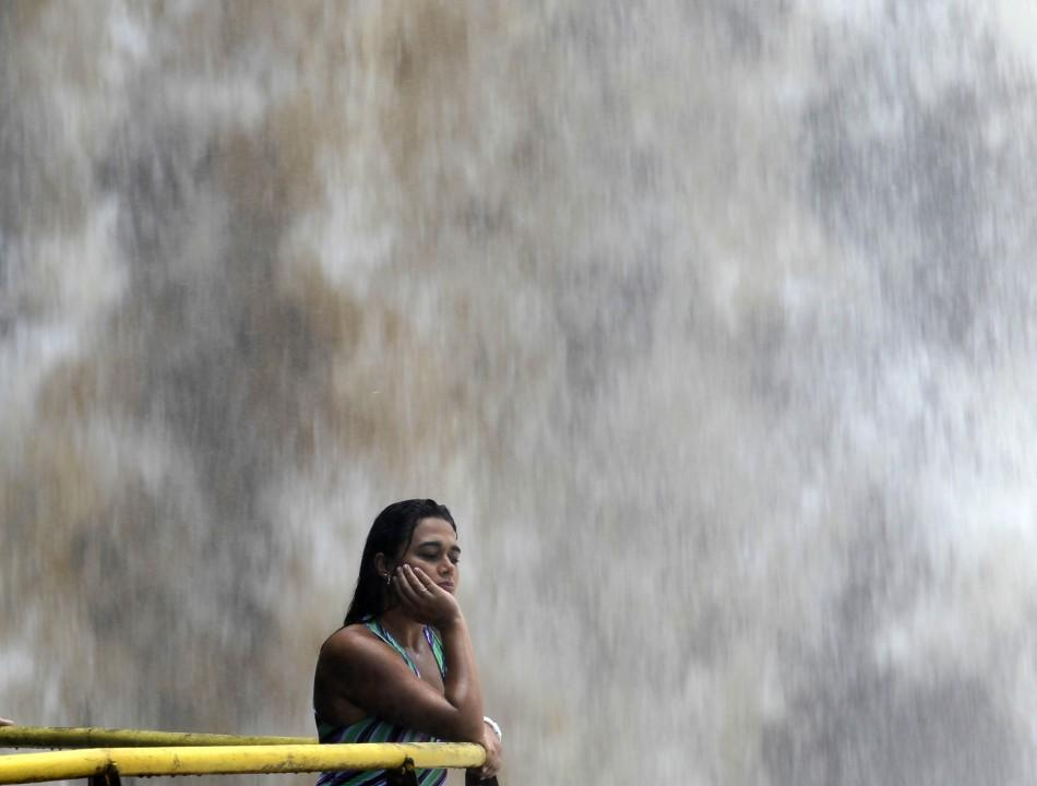 A tourist watches the Iguazu Falls from a viewing point on the border of Argentina's province of Misiones and Brazil's State of Parana.