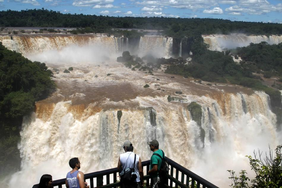 Tourists watch the Iguazu Falls from a viewing point on the border of Argentina's province of Misiones and Brazil's State of Parana.