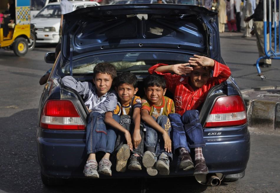 Boys sit in the trunk of a car while travelling on a street in Karachi