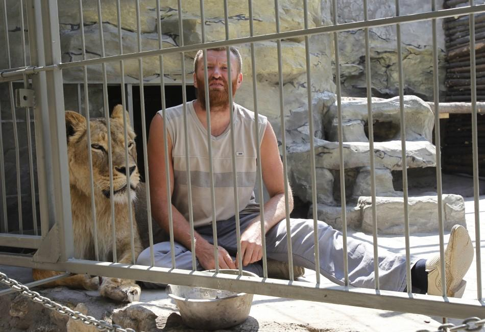 Zoo owner Pylyshenko sits inside a cage with female African lion Katya at a private zoo situated in his yard in Ukraine