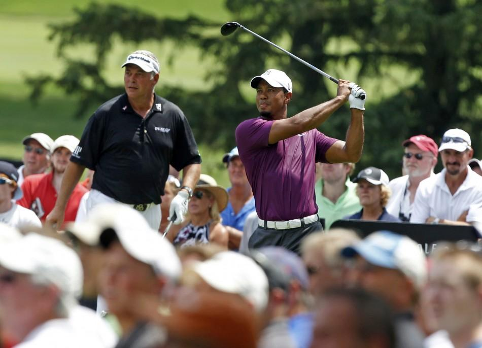Tiger Woods of the U.S. tees off on the third hole as his playing partner, Northern Ireland's Darren Clarke looks on during the first round of the WGC Bridgestone Invitational PGA golf tournament at Firestone Country Club in Akron