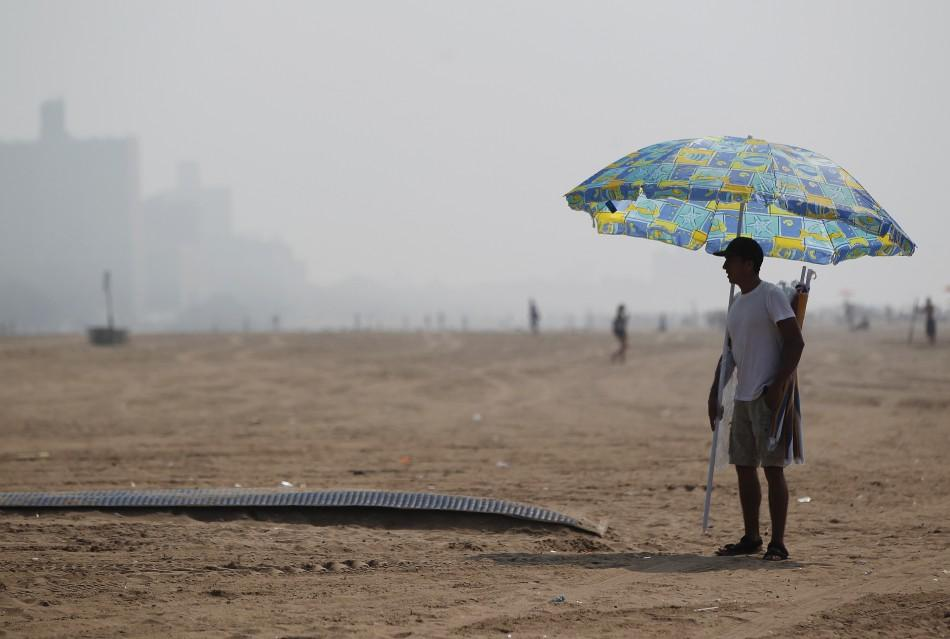 A man stands with an umbrella at Coney Island in the Brooklyn borough of New York