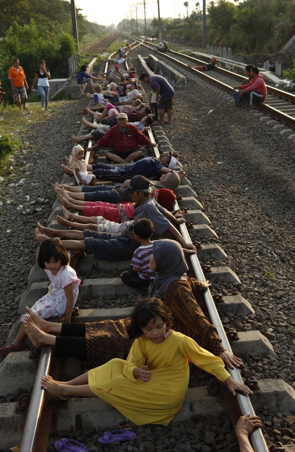 Residents lie on railway tracks in Rawa Buaya in Indonesia's West Java province.