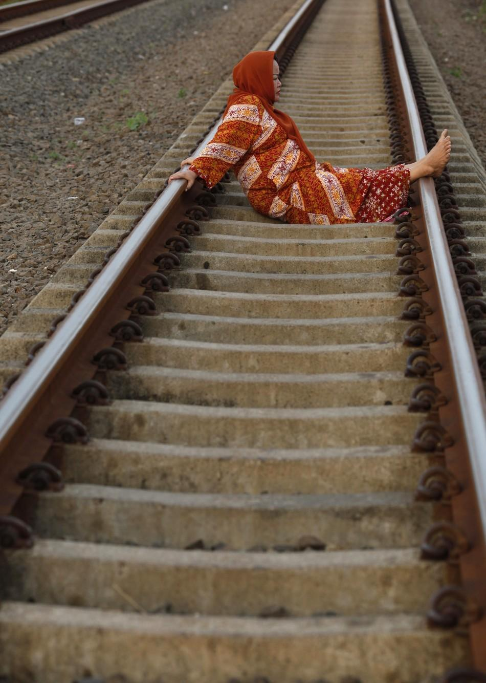 A woman lies on railway tracks in Rawa Buaya in Indonesia's West Java province.