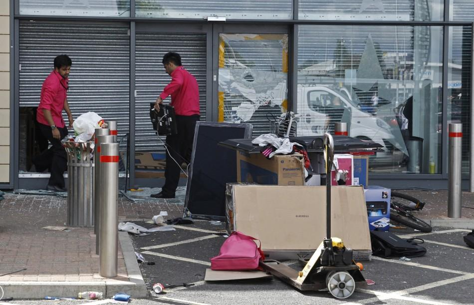 Staff at an electronics goods store clear up after looters damaged the shop at the Tottenham Hale Retail Park in Tottenham, north London.