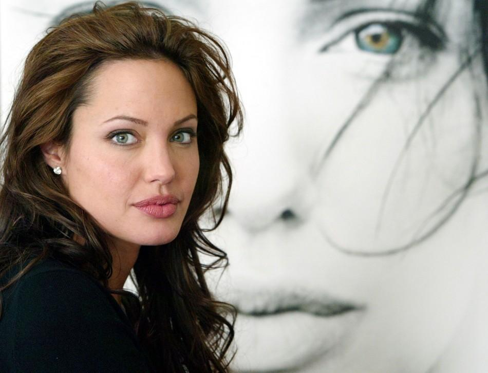 ACTRESS ANGELINA JOLIE POSES NEXT TO A POSTER FOR HER NEW FILM.