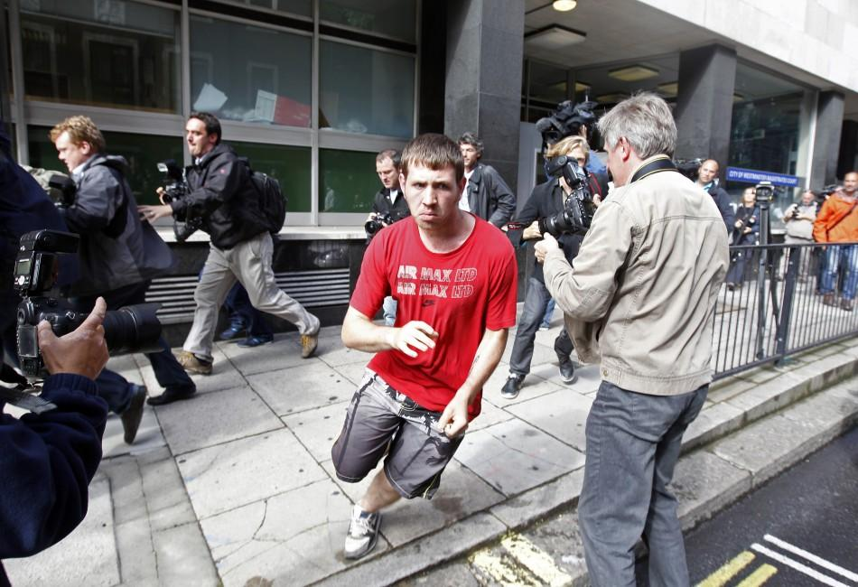David O'Neill aged 22 attempts to avoid the waiting media as he runs from City of Westminster Magistrates' Court after he was released on bail, on charges relating to the London riots, August 11, 2011.