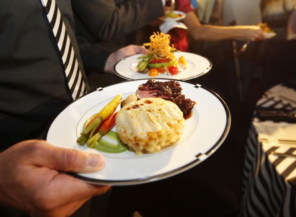 A waiter carries the main course featuring filet mignon and macaroni and cheese gratinee and salad featuring heirloom tomatoes for the 2011 Creative Arts and 63rd Primetime Emmy Awards Governors Ball during a press preview in North Hollywood, California