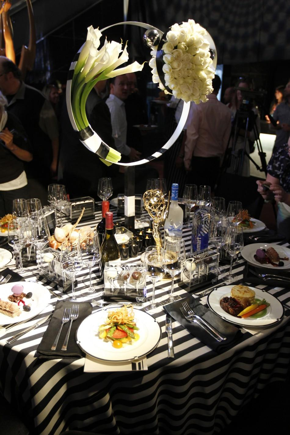 An Emmy statuette is pictured on the table presenting the table setting and theme, mod illusions, and salad course featuring heirloom tomatoes for the 2011 Creative Arts and 63rd Primetime Emmy Awards Governors Ball during a press preview in North Hollywo