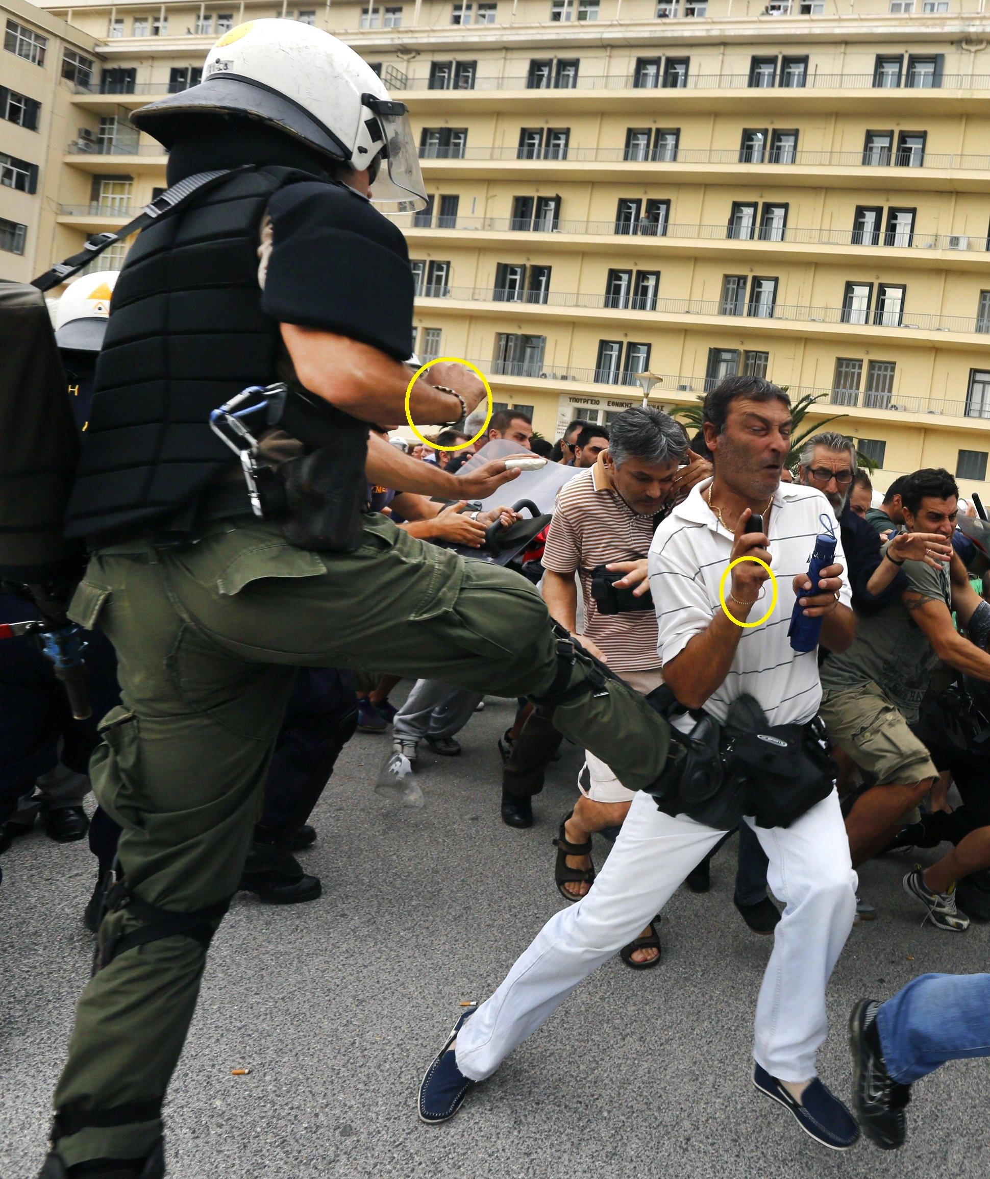 A riot policeman kicks a demonstrator during a protest at the Ministry of Defense on October 4.