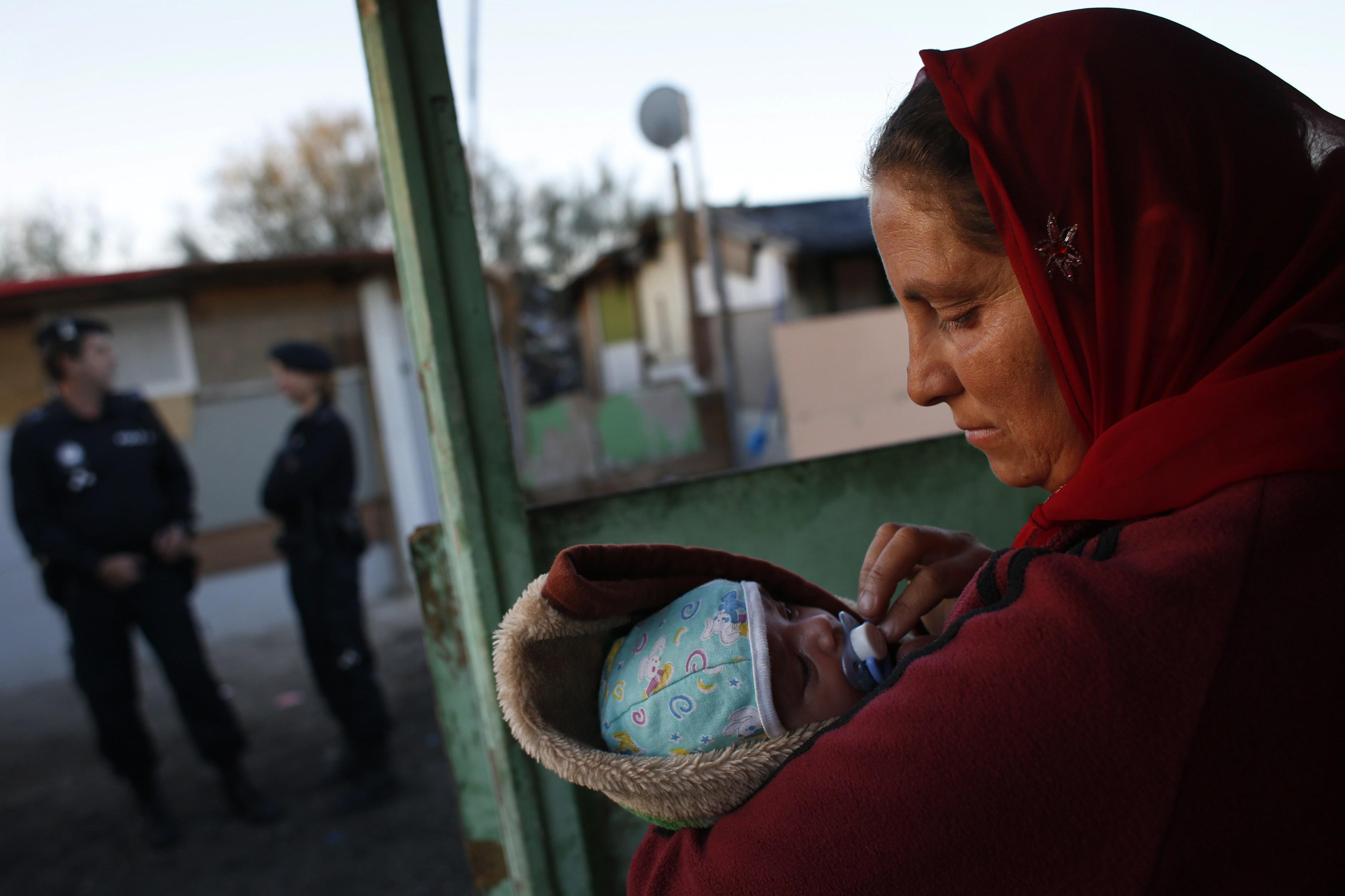 "Angela holds her one-month-old son Raul as police officers block the way while an excavator demolishes a neighbor's shack in Madrid's ""El Gallinero"" slum."