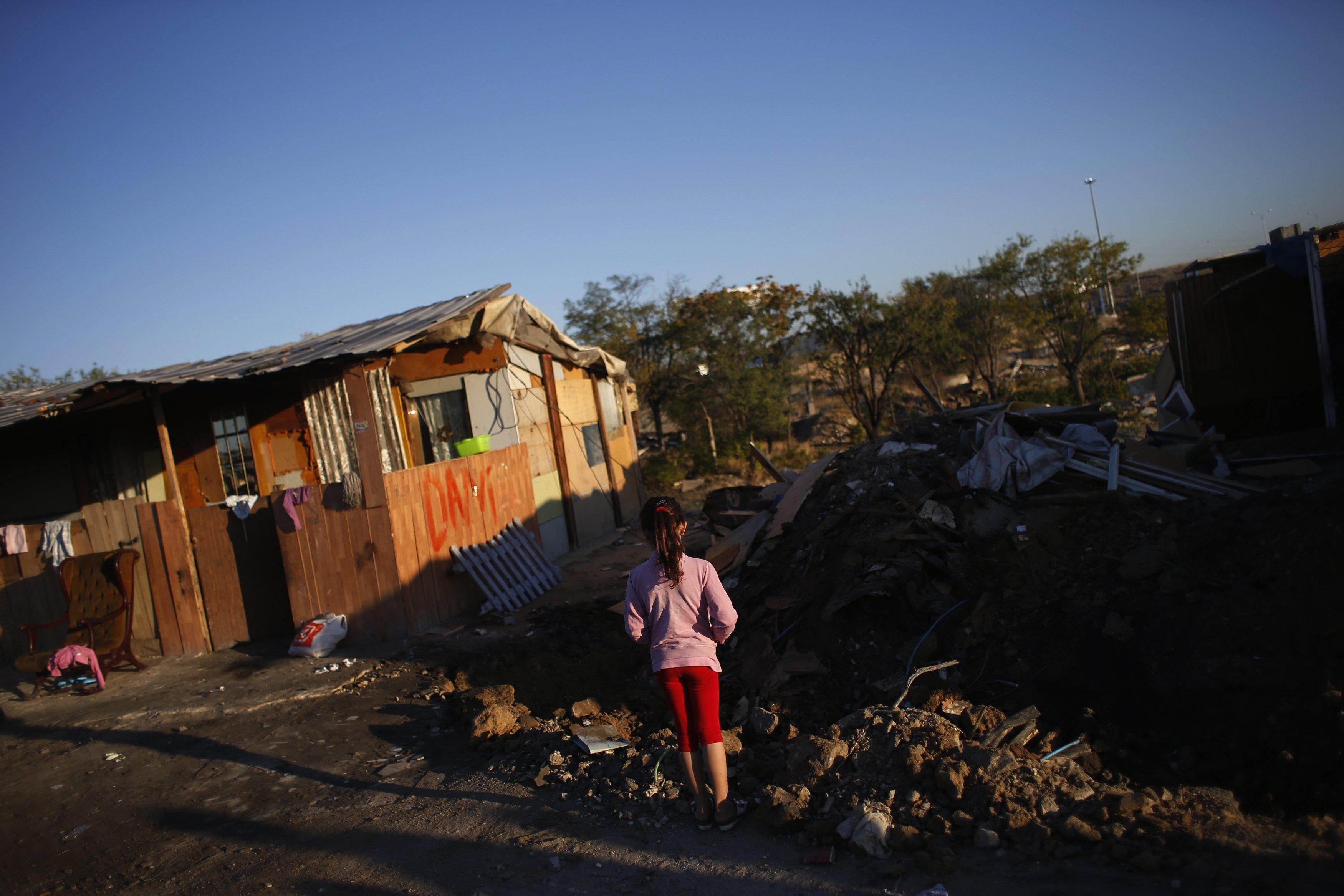 "A girl looks at the remains of a relative's shack after it got demolished in by police in Madrid's ""El Gallinero"" slum."