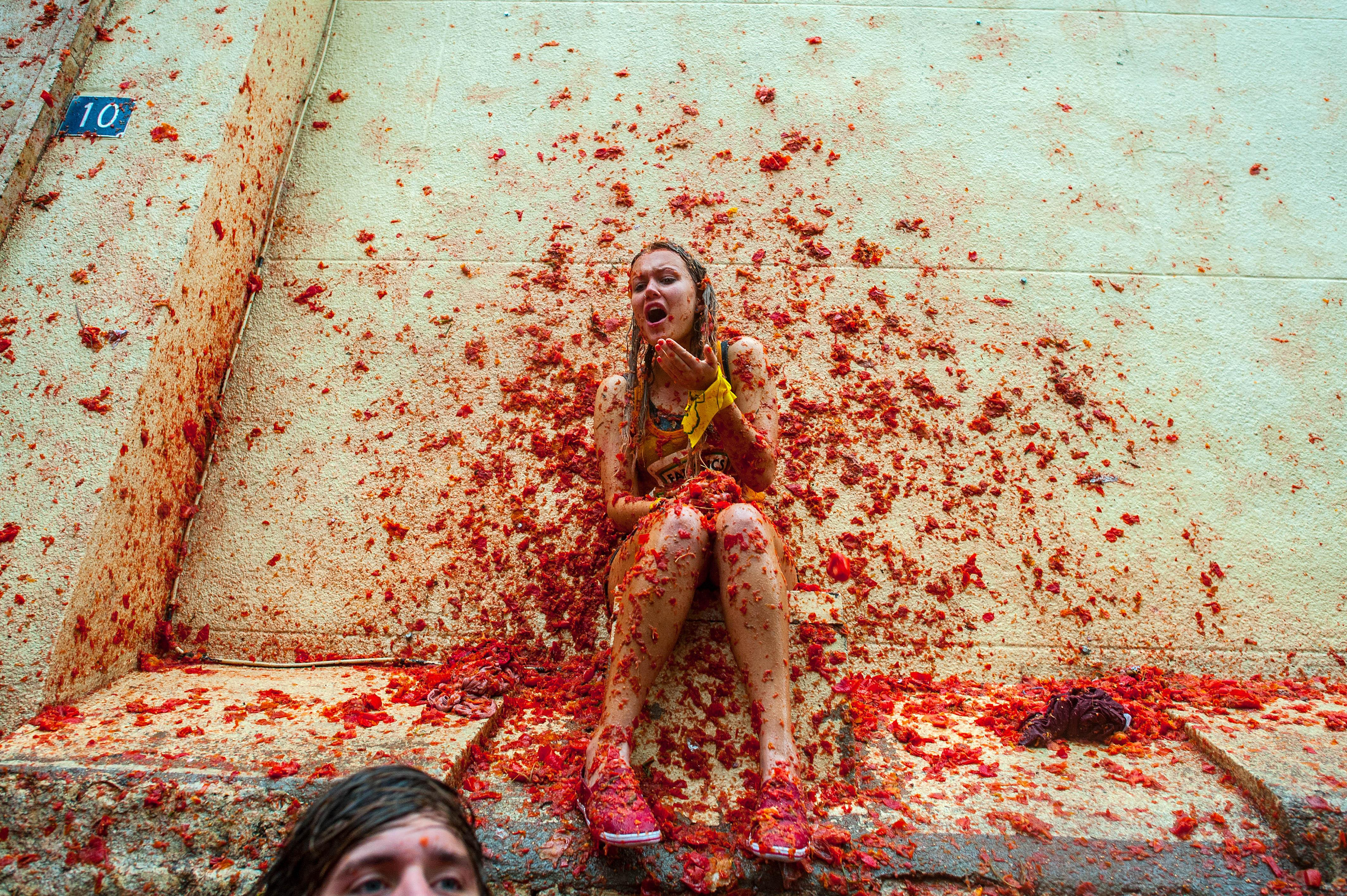 A women at La Tomatina is hit by tomatoes