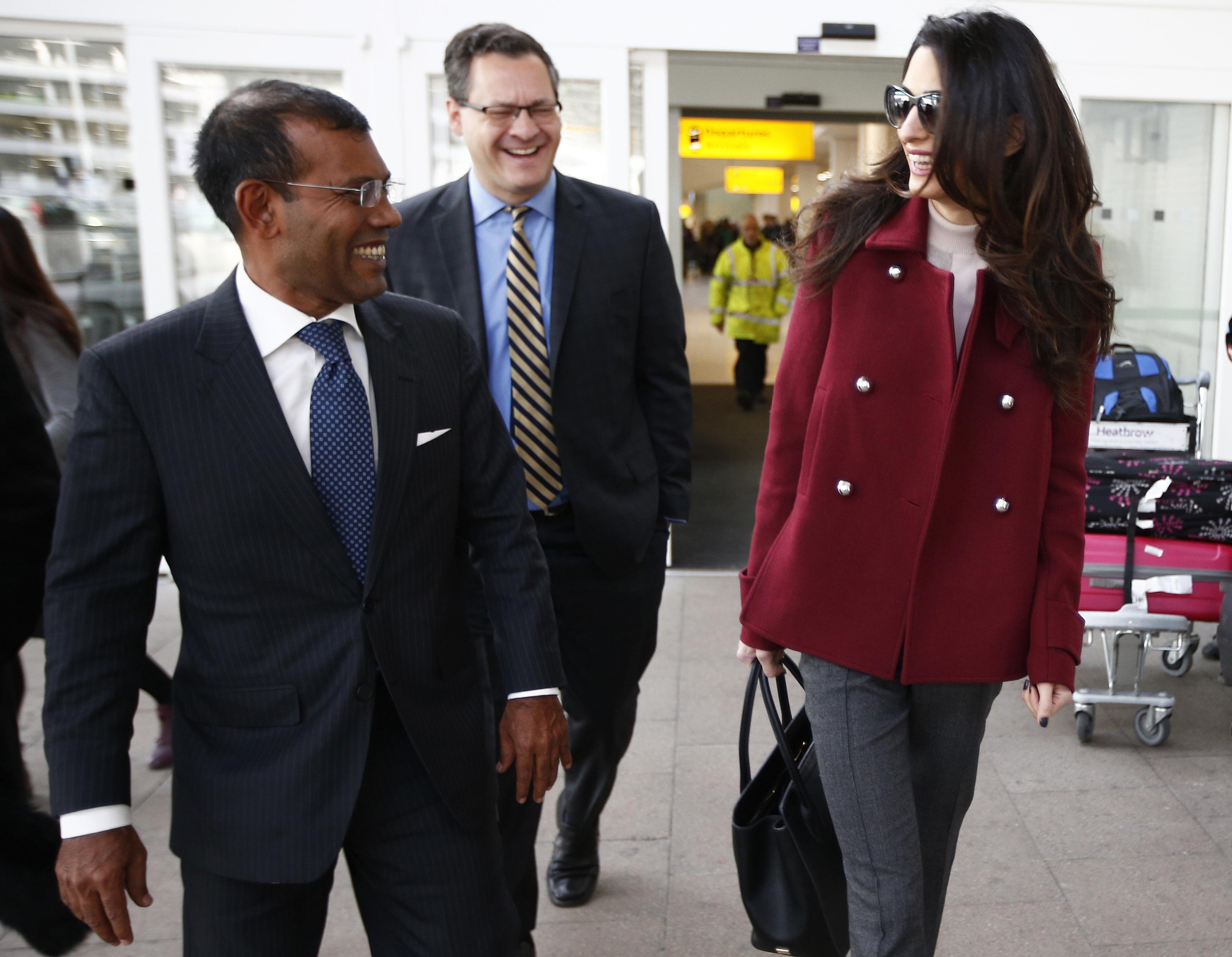 Lawyer Amal Clooney walks with the deposed President of the Maldives Mohamed Nasheed