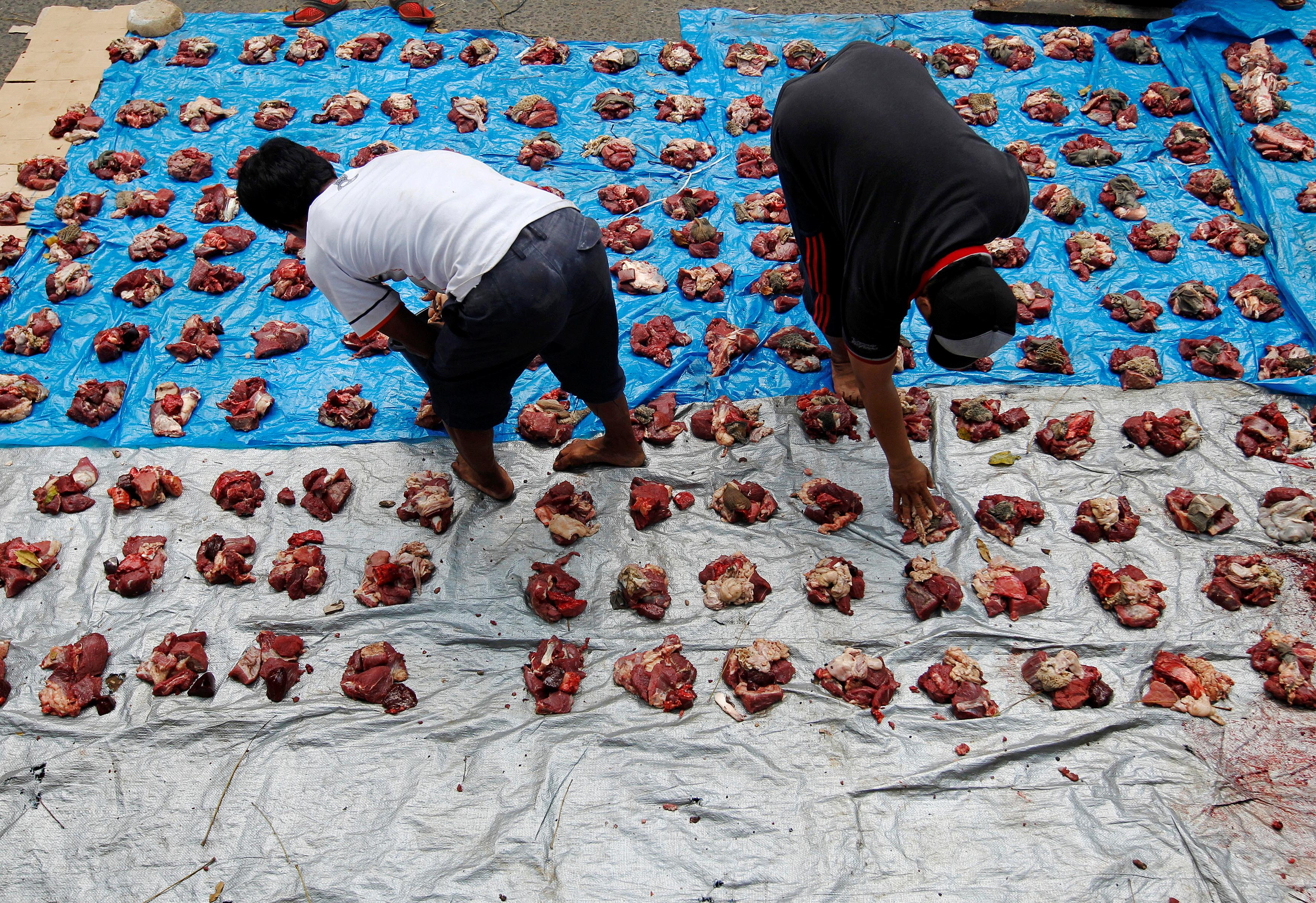 Men put out freshly slaughtered goat and cow meat for donation to the poor during Eid al-Adha festival near a mosque in Jakarta, Indonesia Sept. 12, 2016. Photo: REUTERS/Iqro Rinaldi