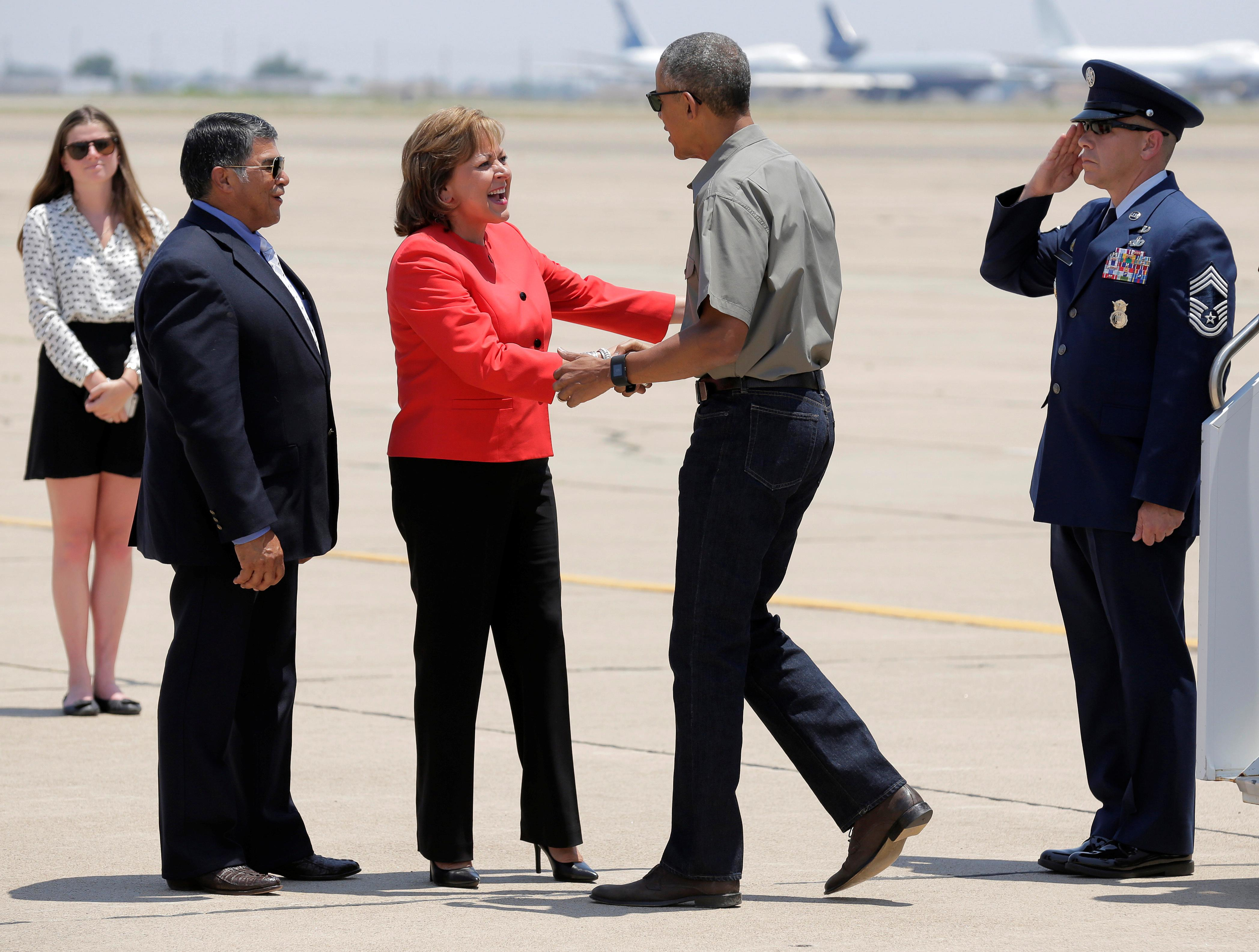 U.S. President Barack Obama is greeted by Governor of New Mexico Susana Martinez as he walks from Air Force One in Roswell, New Mexico, U.S., June 17, 2016.