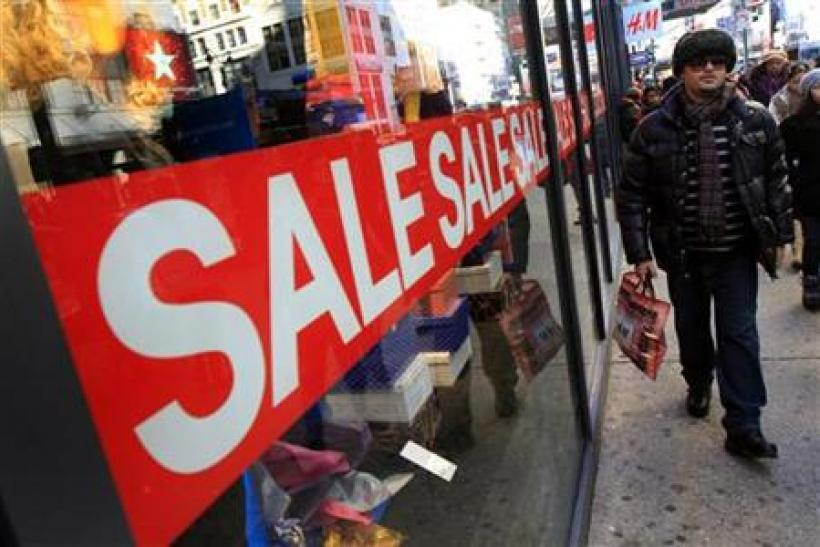 A holiday shopper passes a sale sign at a clothing store in New York